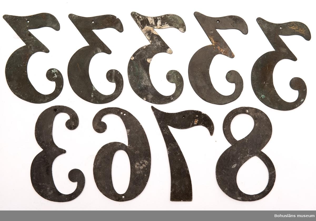 9 psalmnummersiffror av bly och mässing,  höjd 15 cm.  3, 3, 3, 3, 3, 3, 6, 7, 8. UM005660:020-028.  Ur handskrivna katalogen 1957-1958: Trälåda m. siffror för psalmnummer 1-8: Bly. H.: 16 cm, m. utsirningar 9-19: Bly. H.: 9 à 10 cm; m. utsirningar. 20-28: Bly o mässing. H.: 15 cm. 29-31 Bly H.: 13 cm. 32-42: Bly o mässing. H.: 10 cm. 43-51: Bly o mässing. H.: 7 cm. 52-54: Gjutna av gulmetall. H.: 10 cm. 55-56: Vitmålad järnplåt. 57: Bly. H.: 10,5 cm.  Lappkatalog: 13