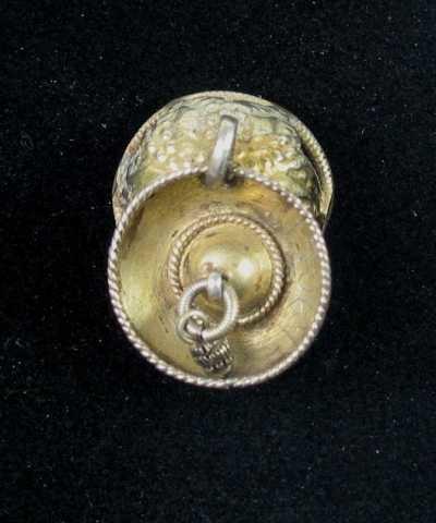 Drevet malje av forgylt sølv med skåleløv. Bunnen, som er tilklipt av sølvblikk og ender i små bladspisser, er mønstret med drevne eller dorete små punkter. Rundt kanten er det en ring av skruetråd. Tvers over ringen er det loddet en tynn sprosse. I en stor løkke midt på bolen henger det et forgylt skåleløv som igjen bærer en mindre løkke med ring og krusedobbe. I bunnen og langs kanten er det lagt en tvinnetrådsring. Ingen synlige stempel.