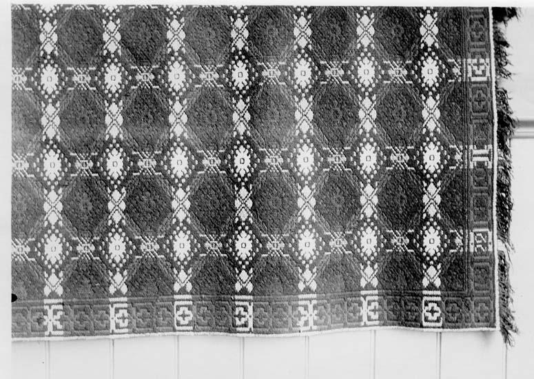 """Del av ett finnvävstäcke daterat 1822 med mönster som benämndes """"Rosor och grenar""""."""
