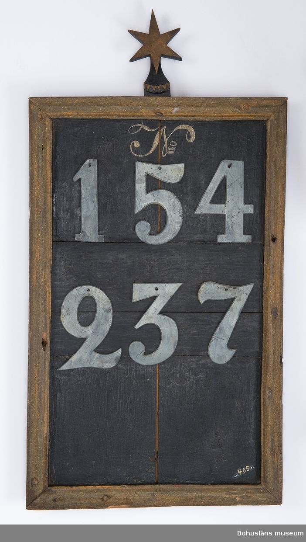 """Psalmnummertavla av trä för att hänga upp nummer på psalmer som ska sjungas under en gudstjänst. Framsidan hopfogade svartmålade trädelar, överst målat """"No"""", inramat av en ockragul målad ram. Krön bestående av sexuddig stjärna. På baksidan ett limfärgsmåleri, barockdekor i form av en akantusslinga. I övre kanten målat """"ANNO 1732 L : P"""". Ur handskrivna katalogen 1957-1958: Nummertavla 1732 Lane Ryr H, utan stjärnan: 62,5 cm. Br. 39 cm; trä, profil. ramlist, upptill 6-uddig stjärna.  6 tillk. siffror av bly, vitmålade, etta, tvåa, trea, fyra, femma, sjua, nr 405 b - 405 g. Föremålen oskadade."""