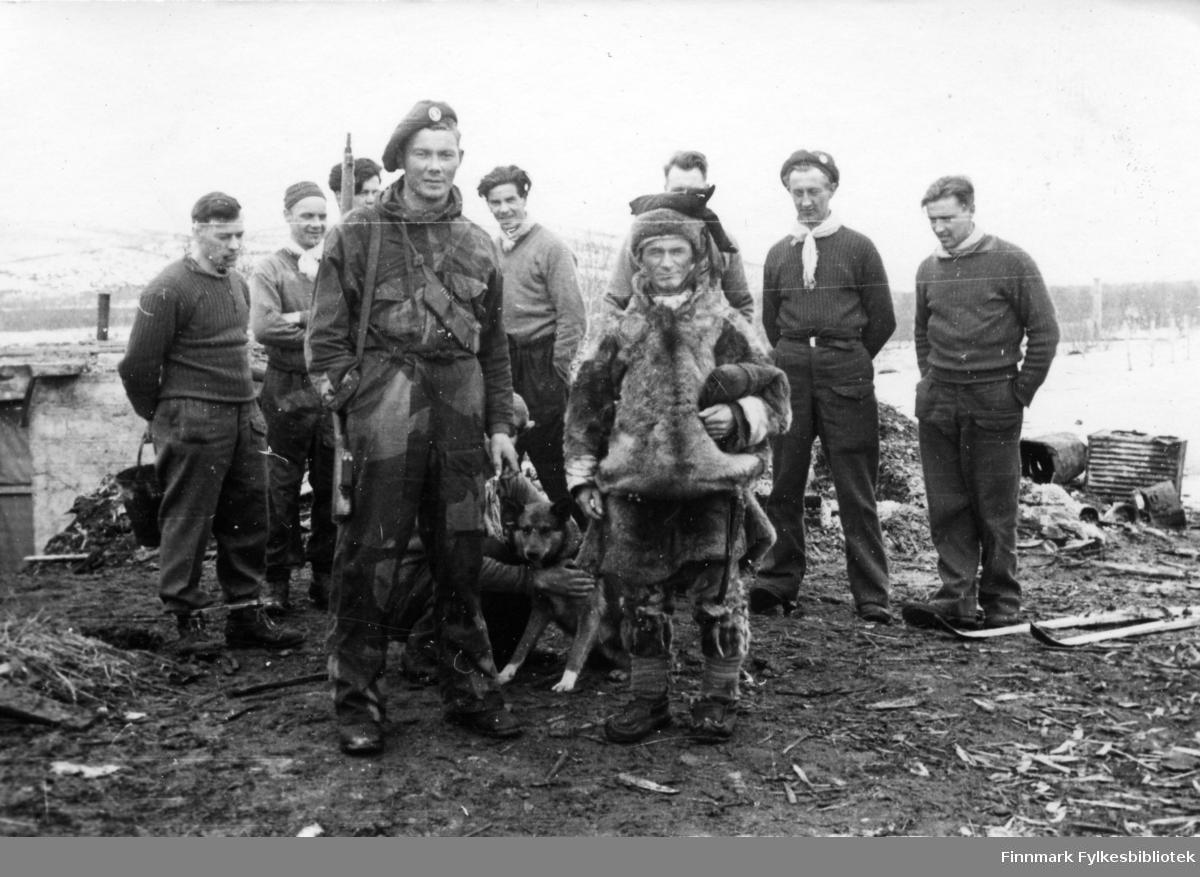 """Gruppebilde. Menig soldat Johan Edvind Aslaksen (27.06.1920)  fra Karasjok fra Den norske Brigade, 2. Bergkompani. Fotografert i  Børselv. Til høyre for Johan står stifinner og kjentmann Per Nilsen Gaup fra Karasjok i samisk lue og pesk, han var reinvokter i Børselv.  Per Nilsen Gaup, eller Nils Gaup bodde i ei lita hytte ved Børselva. Han gikk senere bort på Solbrått aldershjem. Kirsten Anne Vedhugnes var søster til Per Nilsen Gaup, de var i alt ti søsken.  Mange norske reindriftssamer på innlandet unndro seg tvangsevakueringen høsten 1944 og rømte innover vidda mot Sverige og Finland med reinflokkene sine. De kunne derfor forsyne soldatene med ferskt reinkjøtt og ikke minst, bistå med transport og de hjalp soldatene med orienteringen. En av soldatene minnes """" Samene, vet du, de var våre gode hjelpere. De var skikkelige nordmenn og lånte oss både reinsdyr og hester. De kjente terrenget og var gode på kart og kompass. Underveis rekrutterte de norske styrkene også lokale folk fra Finnmark, både kvinner og menn, mange av dem hadde tidligere bodd i huler i Finnmark, i skjul for tyske soldater. Bildet må være tatt vinteren 44/45.   Bildeserien """"Frigjøringen av Finnmark 1944-45"""" viser et unikt materiale fotografert av soldater i Den Norske Brigade, 2. Bergkompani under deres oppdrag """"Frigjøringen av Finnmark"""" som kom i stand under dekknavn """"Øvelse Crofter"""". Fakta rundt dette bildematerialet illustrerer iflg. vår informant, George Bratli: """"2.Bergkompani, tilhørende Den Norske Brigade i Skottland,  reiste fra Skottland 30. oktober 1944 med krysseren «Berwick» til Scapa Flow på Orkenøyene for å slutte seg til en større konvoi som skulle være med til Norge. Om bord på andre skip var det mange russiske krigsfanger som hadde vært på tysk side og som nå ble sendt hjem.  2.Bergkompani forlot havn 1.november 1944 og kom til Murmansk, Sovjetunionen, 6. november 1944.  De ble her lastet om og fraktet til Petsamo, Sovjetunionen, hvor de ankommer 11.november 1944.  Kompaniet reiser s"""