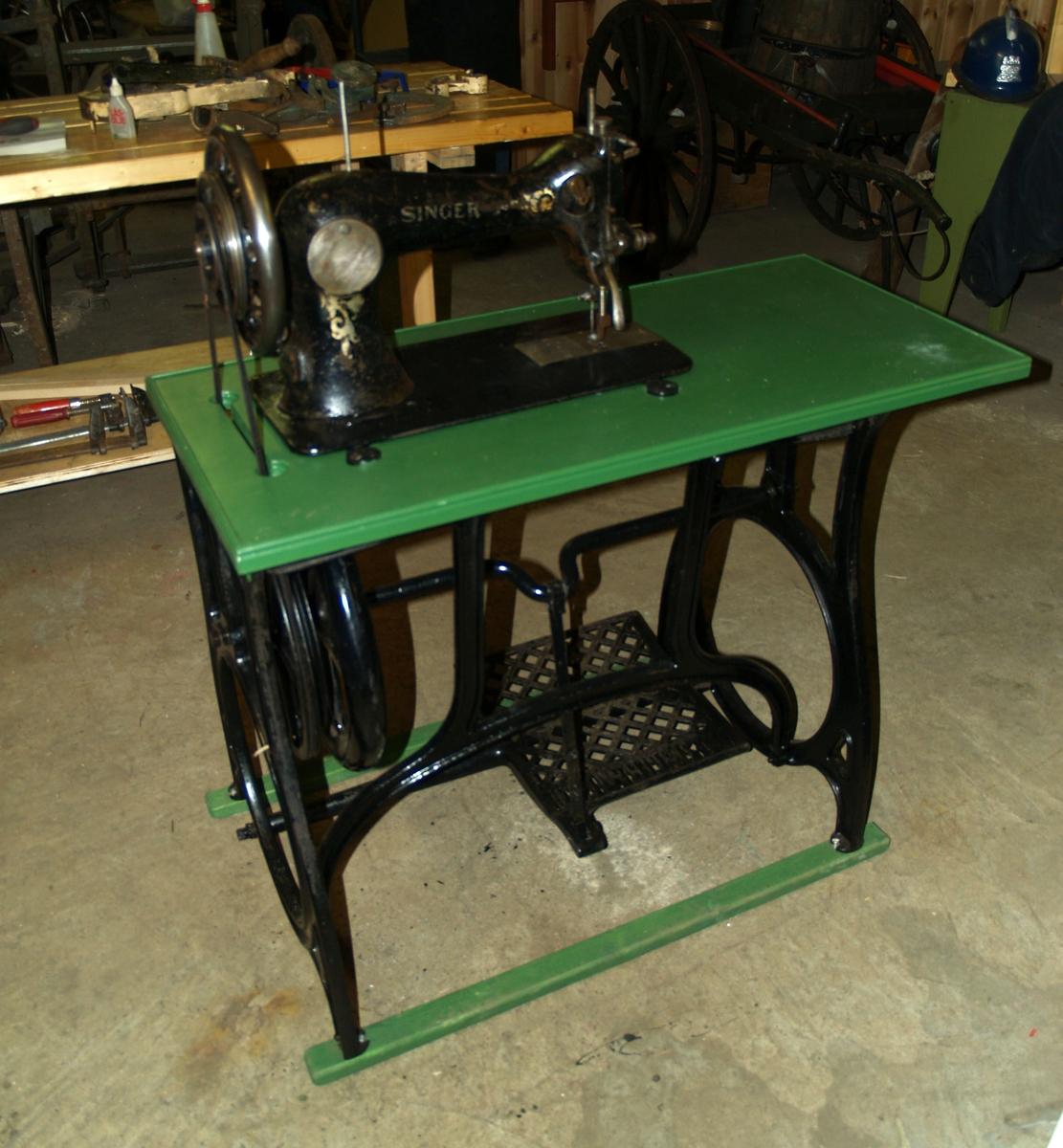 Symaskin med pedaldrift og montert i bord. Reimdrift fra hjul på understell til symaskinen. I Brannvesenet ble den bruk til sadelmakerarbeid og annet sømarbeid.