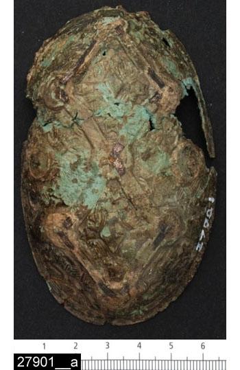 """Anmärkningar: Badelunda sn, Tuna undersökt 1952-1953 Spännbuckla, från båtgrav daterad till yngre järnålder, 850 e.Kr. (Vikingatid)  Spännbuckla av brons från grav 75. 1 st samt 2  fragment av nålen av järn varav en del från nålfästet. Spännbucklan tämligen välbevarad, men alla knoppar saknas. Ornerad med gripdjur och ett ramverk med fiskbensmönstrade silverband (bild 27901__c). Större delen av nålen är lös (bild 27901__d). I ena änden en lagning med ett på insidan fastnitat bronsbleck och i samma ände finns ett litet runt hål. Funnen vertikal på högkant. I botten mot fören. Inuti fanns textil- och benfragment. Typ P37. Utställd Forntid 2014 L 103 mm Br 63 mm.  Föremålet har konserverats inför utställningen """"Kvinnorna i Tuna"""" 2008. Se Konserveringsrapport i museets arkiv från Acta KonserveringsCentrum AB, diarenr: 080084.  Litteratur Nylén, E. & Schönbäck, B. 1994. Tuna i Badelunda. Guld kvinnor båtar I. Västerås kulturnämnds skriftserie 27. Västerås. s 44ff. Nylén, E. & Schönbäck, B. 1994. Tuna i Badelunda. Guld kvinnor båtar II. Västerås kulturnämnds skriftserie 30. Västerås. s 112 ff, 150ff, 200.  Fotograferad teckning neg nr A-7422  Analysresultat: Textilfragment, 5 st. Material:Silke. Färg: Gulbrun Bindning: Inslagskypert med två varpar, sk. samitum Trådtäthet: Bindevarp 20tr / cm, z-spunna; fyllnadsvarp 22 tr/cm, z-spunna; inslag 24tr/cm, ej iakttagbar spinningsriktning Mått: största 3 x 7 cm Sidenet är i form av band, 3 cm breda med en 0,3 cm bred vikning i båda sidor. Vikningen nersydd med små stygn. Detta siden kan jämföras med det som A. Geijer beskriver i Birka III, s. 58. Margareta Nockert Stockholm 1970. Rapport i arkivet"""