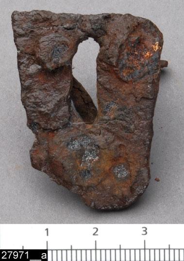 Anmärkningar: Badelunda sn, Tuna undersökt 1952-1953 Beslag, från brandgrav daterad till yngre järnålder, ca 600 e.Kr. (Vendeltid).  Låsskylt av järn från grav 67. 1 st, rektangulärt med två avrundade hörn, tre nitar och i centrum ett 13 mm långt nyckelhål. L 40 mm Br 33 mm  Litteratur Nylén, E. & Schönbäck, B. 1994. Tuna i Badelunda. Guld kvinnor båtar II. Västerås kulturnämnds skriftserie 30. Västerås. s 78f, 86, 200  Fotograferad teckning neg nr A-7419