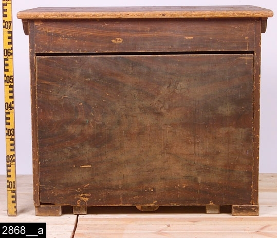 Anmärkningar: Fållbänk, 1800-talets första hälft.  Löstagbar bordsskiva. Fronten går att dra ut, då får man en säng som på bild 2868__b. Djupet blir då 1700 mm. Invändigt är fållbänken gråmålad. Fyra klossformade fötter. H:780 L:920 Dj:690  Hela möbeln är ådringsmålad och bär spår av ett visst naturligt slitage.  Tillstånd: En fot saknas, en fot är lös.  Historik: Inköpt genom vaktmästare Nils Nygren.