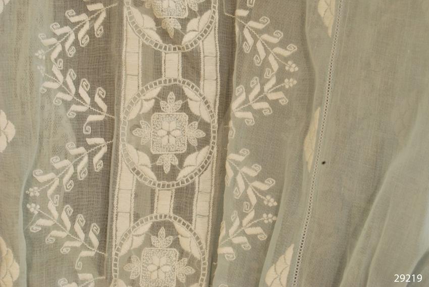 Anmärkningar: Irsta sn Gäddeholm Använd av Elisabeth Lewenhaupt född Beck-Friis 1888 död 1982.  Tvådelad klänning, blus och kjol av ljusblått tunt bomullstyg, bomullsbatist ? Midjekort blus, framknäppt och långa ärmar, ärmuppslag av spets, framtill och runt kragen av sjömansmodell. Ärmuppslagen knäpps med fyra tryckknappar i varje ärm. Både blusen och kjolen försedd med mycket vita broderier i plattsöm, efterstygn och hålsöm. Blusen knäpps med två hakar och hyskor i midjan fram. Kjolen har vit linning och är rynkad. Den knäpps med två hakar och hyskor i midjan bak.