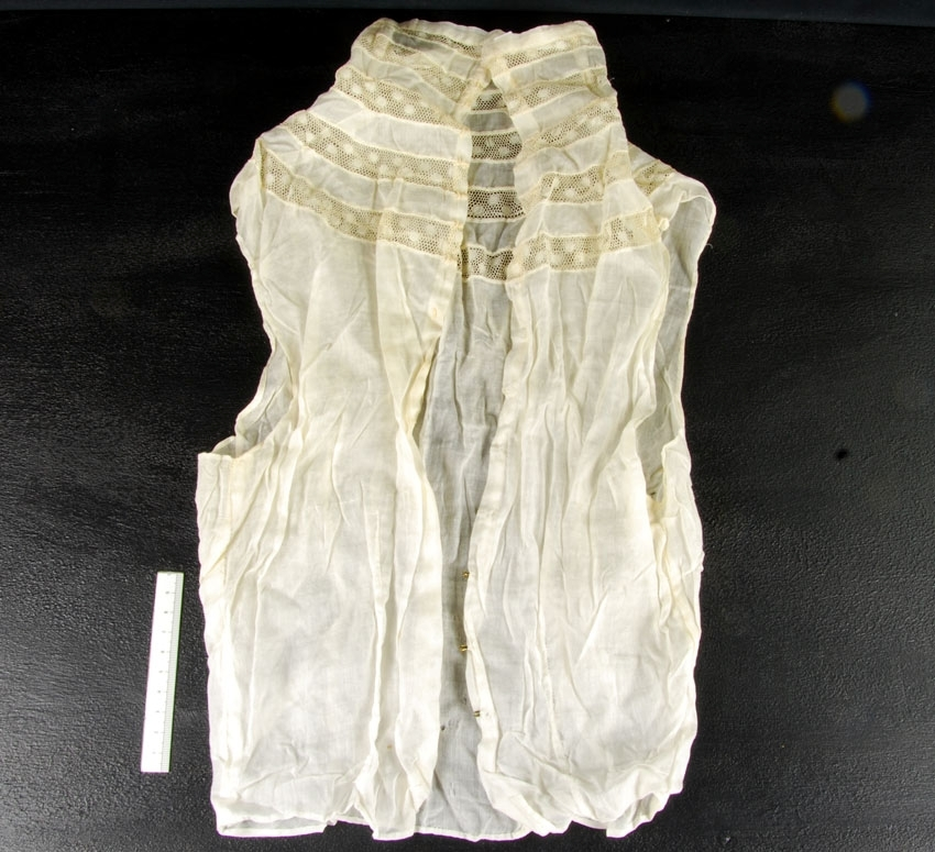 """Anmärkningar: Irsta sn Geddeholm  Krås, 1 st, av cremefärgad bomullsbatist med fem band av infällda spetsar kring halsen och ner över axlarna. Ärmlös. Knäpps i ryggen med med 17 metallhyskor på ena sidan och sydda hakar på den andra. """"Krås"""" till klänning. krås (ty. Krause, av kraus 'krusig'), rynkad eller veckad remsa av fint tyg eller spets, använt som prydnad på skjortbröst (jabot) eller runt hals och på ärmkant i både mans- och kvinnokläder. (Källa NE)"""