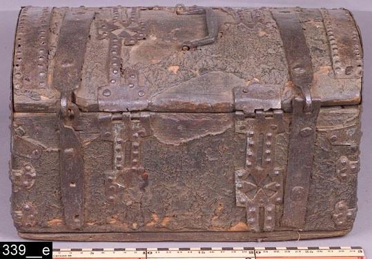 Anmärkningar: Skrin, 1600-tal.  Gångjärnsförsett välvt lock med ett järnhandtag (bild 339__b). Längst fram på locket sitter ett ledat låsbeslag, som låses fast i låset på framsidan. Invändigt är skrinet klätt med papper med handskrivna texter på latin, varav en är lös (bild 339__c-d). Hela skrinet är klätt med läder och är försett med järnbeslag. Beslagen har genombruten dekor bl.a. i form av hjärtan och kors (bild 339__e-f, samt 339__a-b). H:195 B:330 Dj:245  Tillstånd: Nyckel saknas. Läder mellan beslagen saknas på flera ställen.  Historik: Inköpt 1875 från V. Lövsta sn, Stallet för 0,75 kronor.