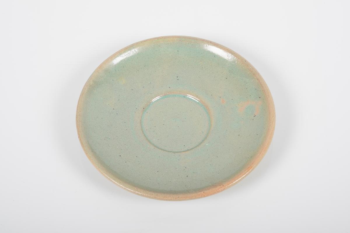 Rund skål i keramikk med grønn lasur. Buet hank på koppen. Skålen er blank på oversiden og matt på bunnen. Det mangler lasur på to små område.