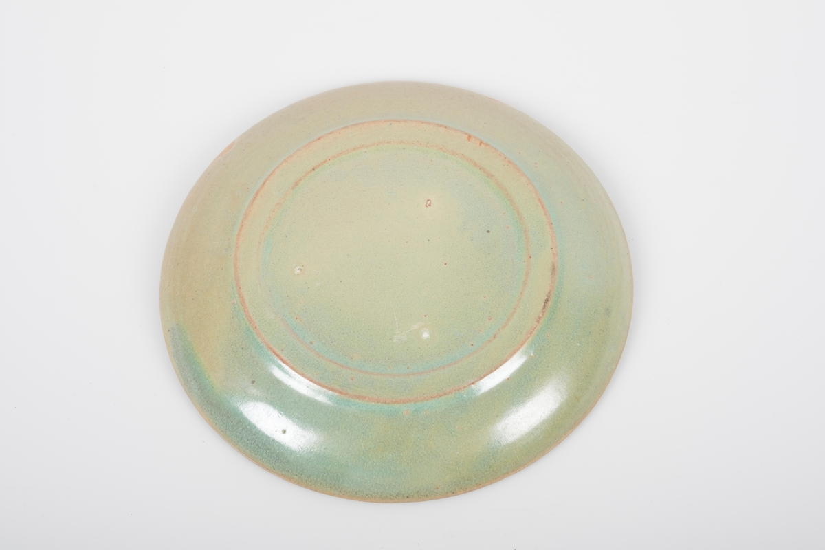 Rund skål i keramikk med grønn lasur. Skålen har spor etter tre knotter på bunnen, usikker funksjon. En hakk på oversiden (produksjonsfeil).