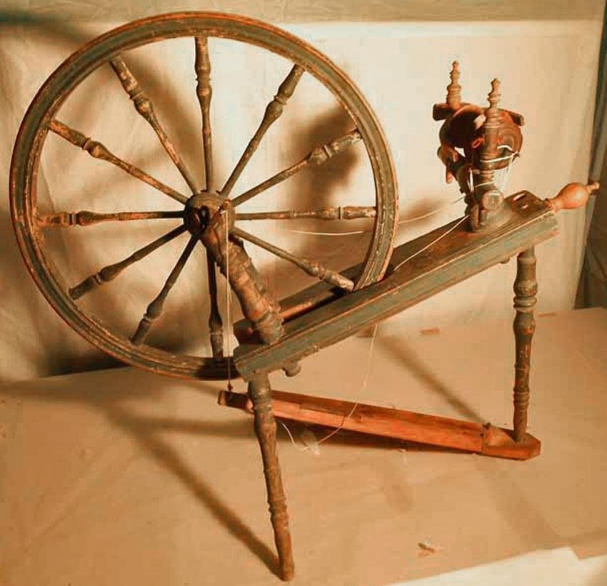 Anmärkningar: Av trä. Tre profilerade svarvade ben. Hjulen har svarvade pinnar. Vinge, rulle och trissa sitter fast mellan profilerade ståndare. Grönmålad. Årtalet 1823. Inköpt på auktionskammaren i Västerås. Kronor 1:50. H; 825. Hjulets diam; 590.