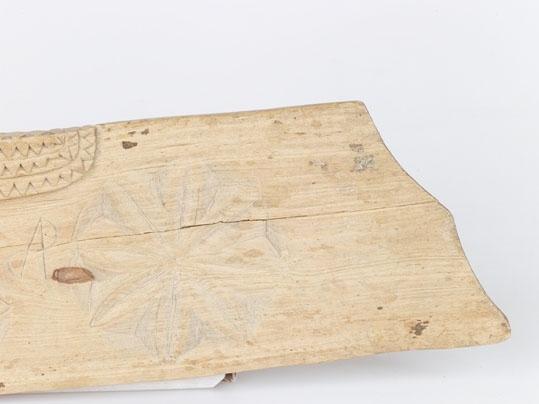 Anmärkningar: Skäktträ av trä, ek, 1805. Består av handtag, och blad med förstärkning utefter halva ryggen. Handtagets skydd och förstärkning ornerade med tre rader triangelformiga inskärningar. Bladet har två stora och två små stjärnor i karvsnitt. Följande inskrift: (tecken som ej har tolkats).  Detta trä överensstämmer till formen och ornamentik helt med Nr-327 F.  Enligt Liggaren köpt för 75 öre 1875.  Plåt Nr-A-2494.