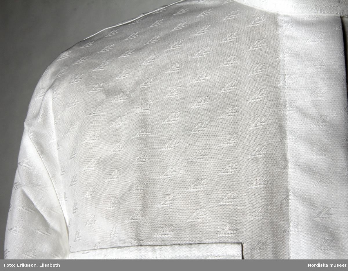 """Blus, storlek 36 / small,  rak modell, av vit bomull. Mönstervävt tyg med linjeflygs symbol i vitt mot vit botten. Ok och ståkrage med knapp av gulmetall med parställda lejon kring sköld med kors under öppen krona. Knappslå med dold knäppning med 7 vita plastknappar och motsvarande knapphål. En bröstficka med lock och vit plastknapp på var framstycke. Två motveck börjande mitt på bakstycket mot oket. Svängd nerkant på blusen.  lång ärm med manschett med samma gulmetallknapp som vid kragen.  På insidan av kragen påsydd vit textiletikett med text i guldfärg """"ETON OF SWEDEN / S / 36"""" Bredvid denna ytterligare etikett med text: """"100% BOMULL COTTON / ETON OF SWEDEN"""" och på baksidan tvättråd. /Leif Wallin 2016-01-11"""