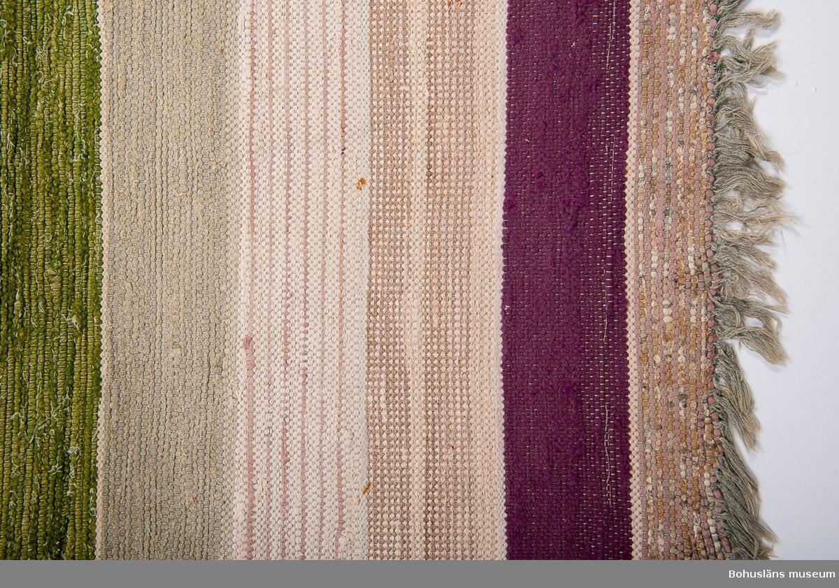 """Matta med bomullsvarp och med inslag av pastellfärgade bomulls- och ylletrasor i rosa, vitt och ljusmelerade toner. Några breda ränder i grönt och lila.  Mattan är i gott skick. Den kan ha varit längre men avkortats med tiden på grund av slitage.  Trasmattan är tillverkad av Gunhild Andrea Arvidsson (1894 - 1981), Gullholmen 5.13, syssling  till Karin, som skänkte det föräldrahem som gjordes till museum, Skepparmuseet på Gullholmen. Ytterligare två systrar finns som idag, varav en lever, f. 1905.  Andreas hem var lika fyllt av saker som föräldrahemmet. En systerdotterdotter ärvde och sålde det mesta på auktion.  Hon  var ogift och gick som ung något år på Tyft folkhögskola på 1920-talet. Hon arbetade något i konserven men var annars mest hemmavid. """"Arvidssons behövde inte arbeta"""".  Även sysslingen Anna tillverkade folkdräktsliknande plagg som hon ibland komponerat själv. Dessa kan ses på skyltdockor på museet på Gullholmen. Systrarna hade också del i gård på Hermanö, """"gårdslott"""", vars lagård idag är Gullholmens konstmuseum. I 60-årsåldern byggde Andrea en sommarstuga på Hermanö, """"Solbacken"""",  vilket alla tyckte var konstigt. Hon vågade dock aldrig övernatta där """"eftersom hon var synsk"""".  En gång gjorde hon illa  benet och då hämtade givarens far (jordbrukare på Hermanö) henne i traktorkärran och tog henne hem till """"vinterhemmet"""", det gula huset alldeles intill affären. På detta sätt skjutsade han henne sedan under flera år. Andrea hamnade på sjukhem 1974. Hon vävde fram till 1960-talet."""