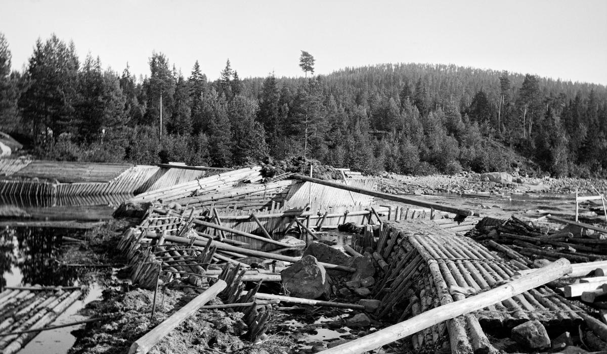 Første fase i ombygginga av Kjellåsdammen i Flisavassdraget i Åsnes i Solør (Hedmark) i 1915.  Fotografiet er tatt seinhøstes, på et tidspunkt da vannføringa i Flisa var meget lav, slik at konstruksjonene var lett tilgjengelige for anleggsarbeiderne.  Da dette fotografiet ble tatt var de «gamle» konstruksjonene - en steinfylt tømmerkistedam - under demontering.  Arbeidet foregikk i ly av en såkalt fangdam, som skulle holde vannmassene unna området der arbeidet foregikk.  Kjellåsdammen var en såkalt atthaldsdam som kunne demme opp den nedre delen av Flisavassdraget i en lengde på opptil fem kilometer.  Den dammen det avbildete anlegget avløste var bemannet med to damvoktere så lenge det pågikk fløting i Flisa.  Tidlig på 1900-tallet var man i tvil om den tilsynelatende begrensete nytteverdien Kjellåsdammen og bemanninga der hadde forsvarte driftsutgiftene.  Det ble snakket om at anlegget samlet lite vann, og at det av den grunn kunne være aktuelt å rive Kjellåsdammen så snart den nedenforliggende delen av vassdraget var bedre «opprenset».  I stedet ble det altså til at man etter rivinga av den gamle dammen bestemte seg for å bygge en ny.  Den nye damkonstruksjonen ble bygd i perioden 1916-24.  Både dammen på tvers av elveløpet og skådammen langsetter elveløpets nordside var opplagt av kvadret naturstein (jfr. bl. a. SJF.1989-02336).