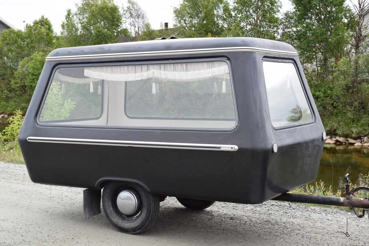 Gravferdsvogn med skyvebrett i bunnen for enkel innføring av kiste. Lys grå gardinkapper med frynsekant med tre dusker i kvitt posement i alle vinduer. Reg.nr.: U-22275. Registrert 30.06.1966