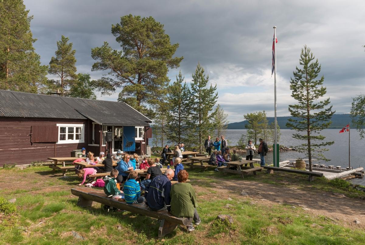Fra arrangementet i forbindelse med 100-årsjubileet for slepebåten «Trysilknut» ved Sørlistøa fløtermuseum ved Osensjøen i Åmot 11. juni 2014.  Fotografiet er tatt på sletta foran huset museet bruker som kafé- og resepsjonslokale, men som opprinnelig inneholdt mannskapsrom og kontor for fløtersjefen.  På benkene sitter noen av de drøyt 30 gjestene som deltok i jubileumsmarkeringa.  Ved strandkanten til høyre i bildet ligger en spillflåte av den typen som ble brukt til å slepe tømmer over innsjøen før Christiania Tømmerdirektion fikk bygd vinteren 1913-1914.    Mer informasjon om båten Trysilknut finnes under fanen «Andre opplysninger».