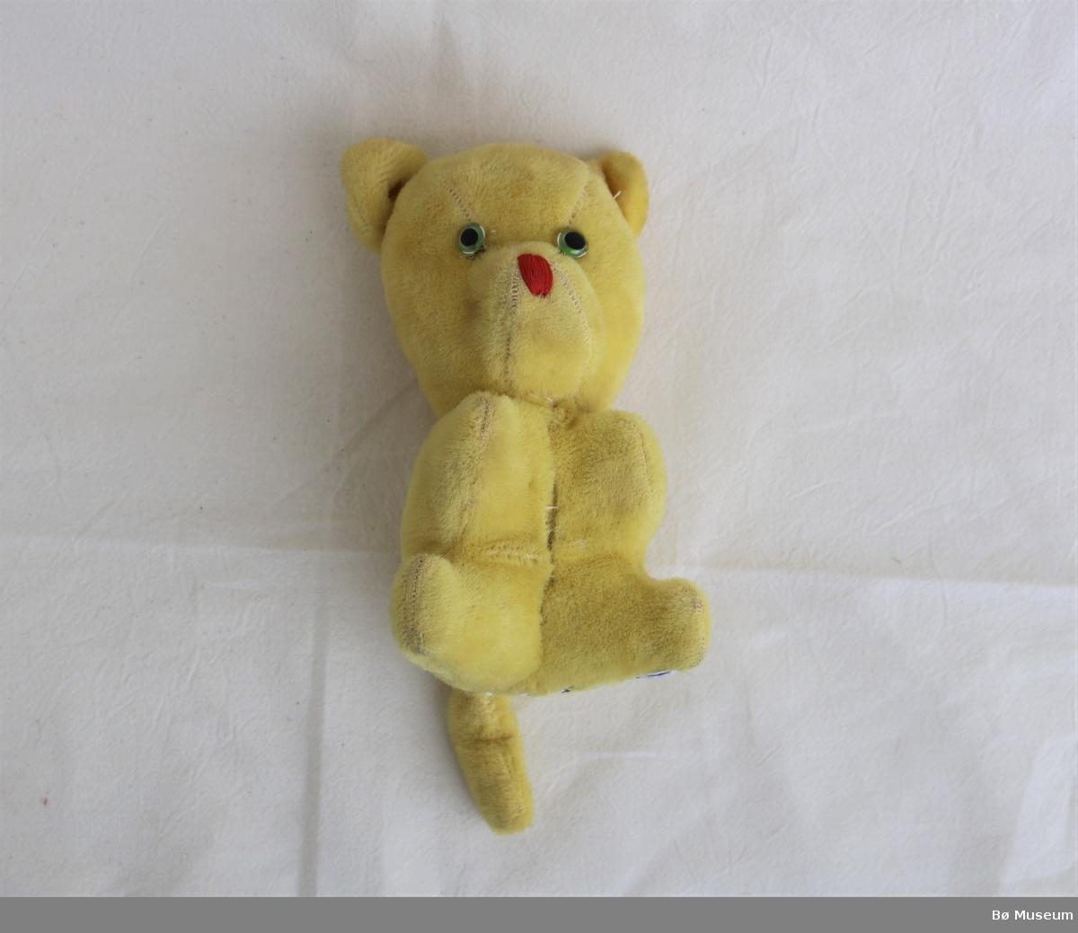 Sittande bjørn med brodert snute, og glasauge som er festa med ståltråd. Søm langsmed mage og rygg samt langsmed beina. Innfelt stykke i hovudet. Påsydde øyre og hale.