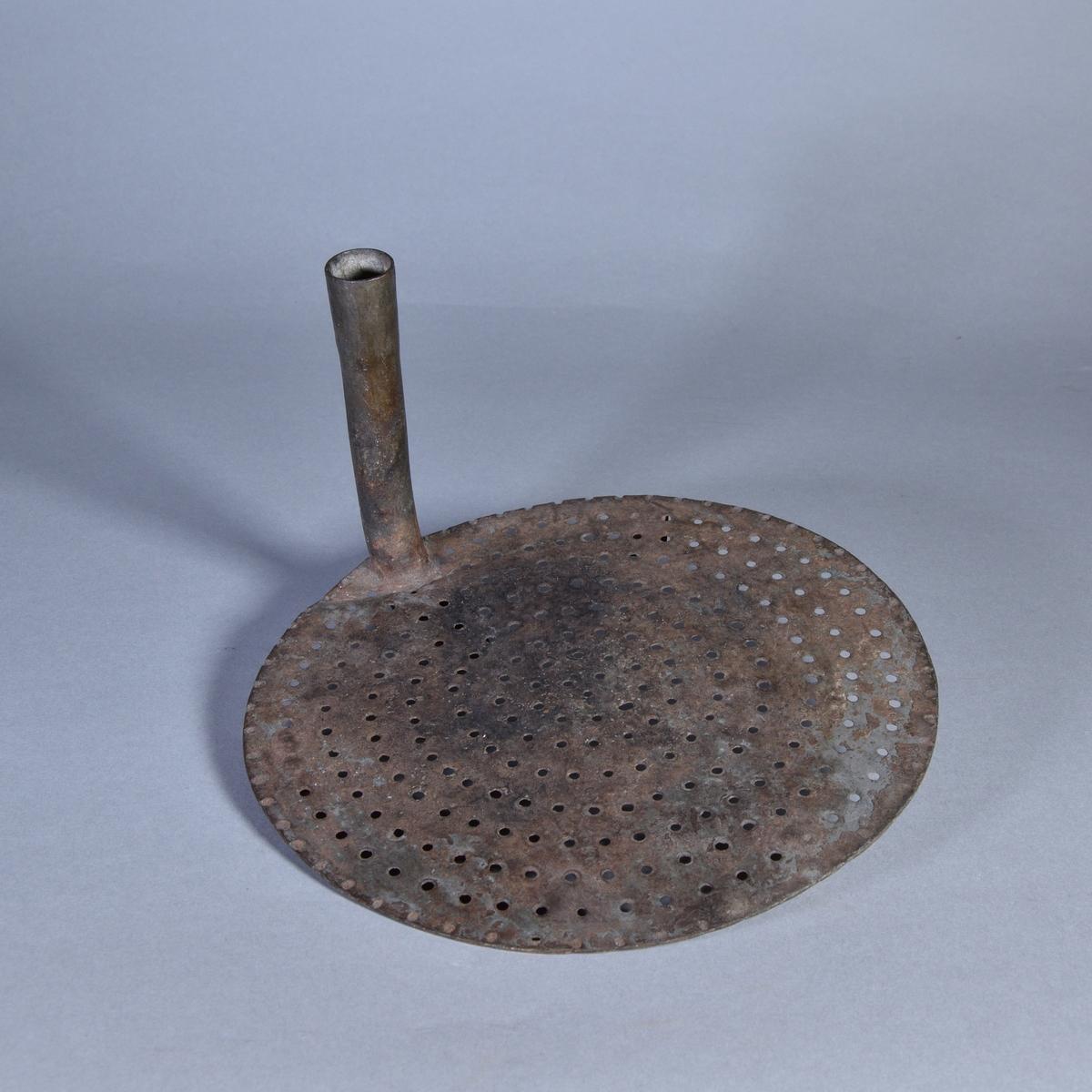 Bunke av metall med rundad botten och utvikt kant. Lös sil av järn på tre låga stöd. I ena sidan av silen pålött böjt rör.