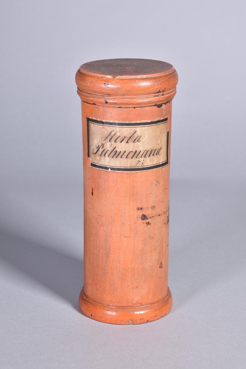 Ståndkärl av rödmålat trä, cylindriskt med plant lock. Svart text inom oval med bandrosett. Sekundär etikett.