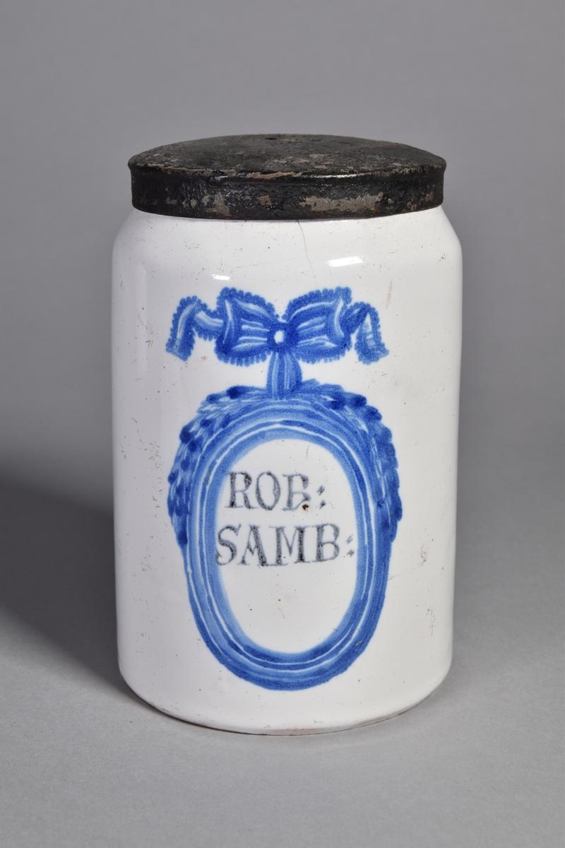 Ståndkärl av vitglaserad fajans, cylindriskt med lock av bleckplåt. Text inom blåmålad medaljong med rosett.