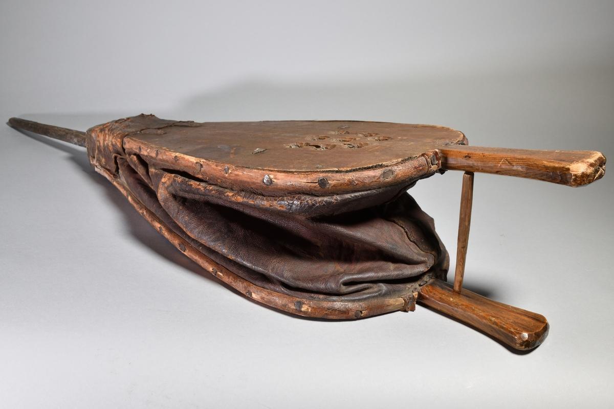Pust, värpust, av trä och läder. Pusten nedåt avsmalnande med rör av järn. Två handtag av trä.