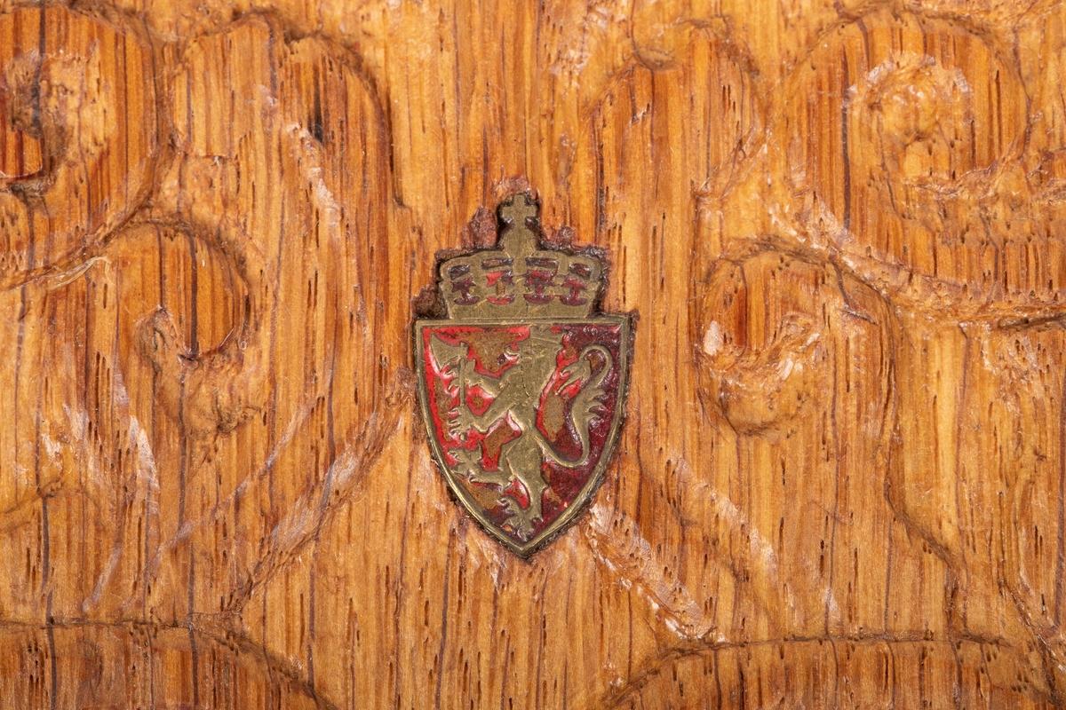 Skjoldet har motiv av en stående, kronet løve av gull som i fremlabbene bærer en øks. Løven kalles ofte Den norske løve. Over skjoldet er en krone med rikseple og kors.
