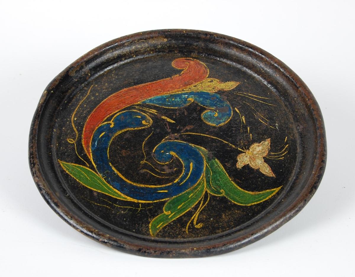 Brett av jernblikk. Brettet er rund i formen med opphøyet kant, svartmalt og med rosemaling  i fargene rødt, blått, gult og grønt. Synes å være blitt lakkert over malingen.