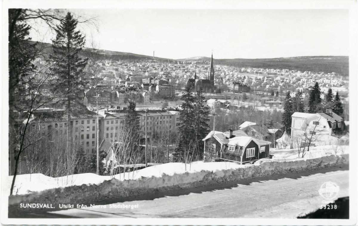 Vy från Baldersvägen västerut ner mot Sundsvalls stadskärna. Det ljusa huset till höger i bild har adress Baldersvägen 20. Vykort.