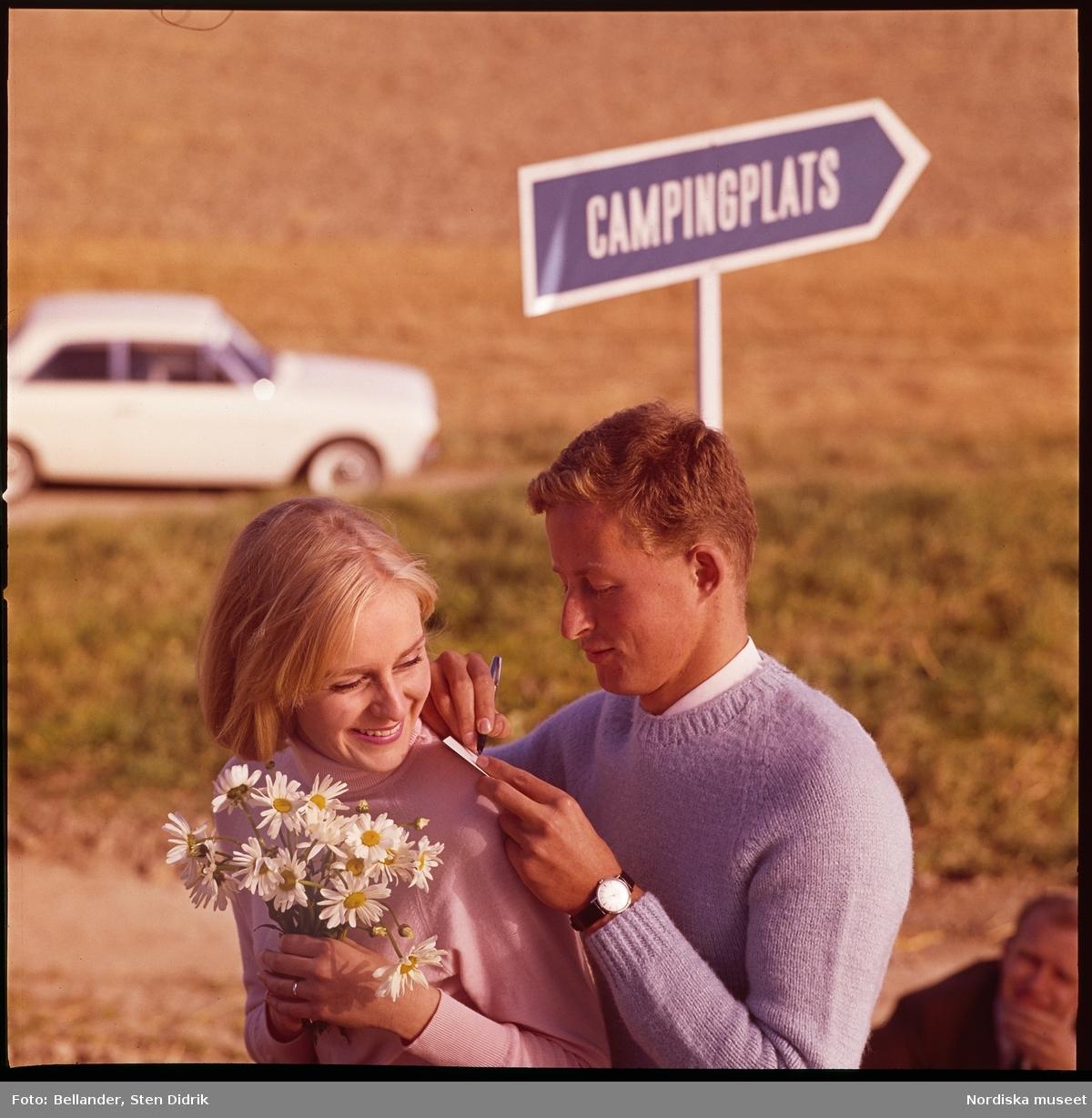 Par skriver kort, skylt och bil i bakgrunden.