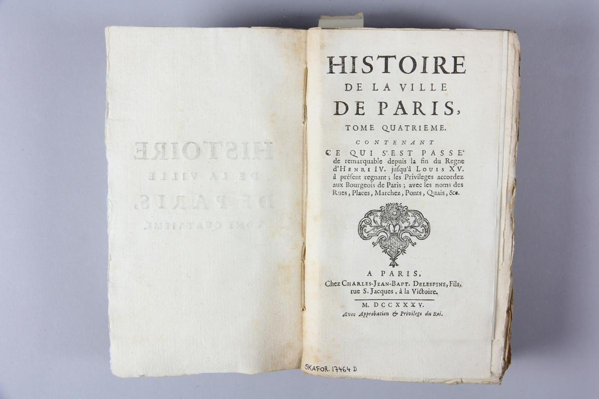 """Bok, häftad, """"Histoire de la ville de Paris"""", del 4, tryckt 1735 i Paris. Pärm av marmorerat papper, oskuret snitt. Blekt rygg med etikett med titel och samlingsnummer. Ej uppskuren. Karta över Paris."""