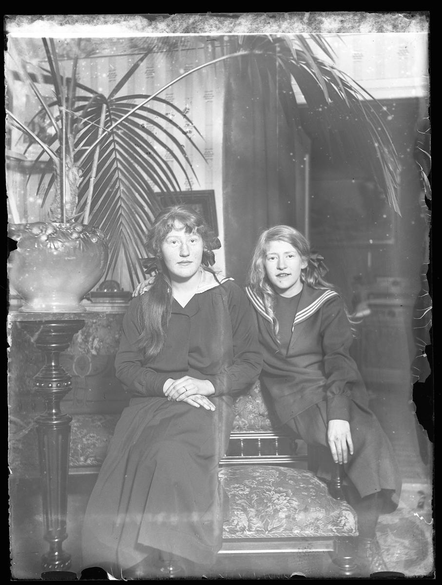 Porträtt av Gerda och Vera Larsson sittande på varsitt armstöd till en stol. Den yngsta flickan har mörk sjömansklänning och rosett i håret medan den äldre har en mörk klänning med tunn vit bomullskrage. Bredvid dem står en stor palm på en piedestal.