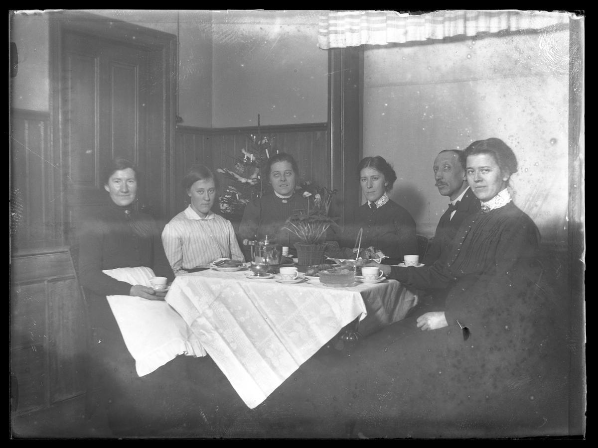 """Fem kvinnor och en man sitter vid ett dukat kaffebord och bakom dem står en klädd julgran. I fotografens egna inventeriekatalog står """" mor mfl."""""""