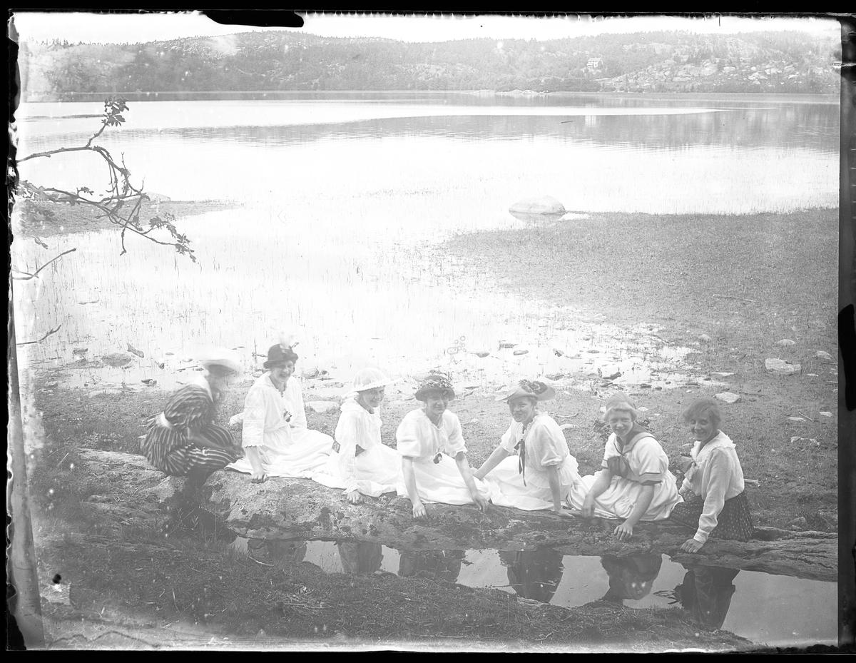 Ruth, Greta, ej namngiven flicka, Ebba, Tulli, Signe och ej namngiven flicka sitter i sommarkläder på stranden vid Mjörn.