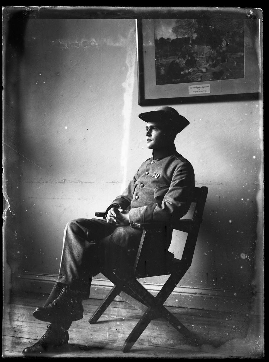 Einar Olsson porträtterad när han sitter på en stol och röker klädd i grå militäruniform.