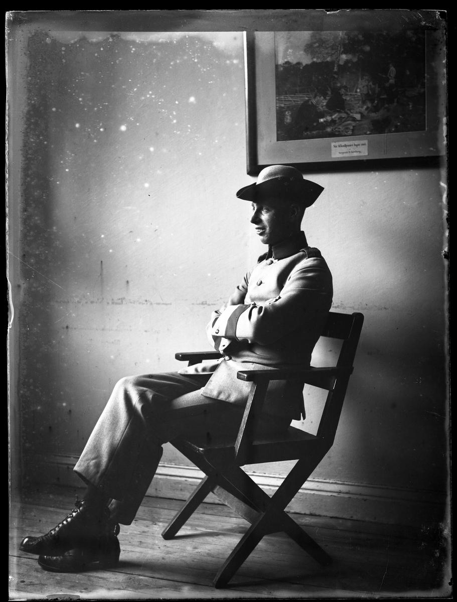 Herr Hansson porträtterad klädd i grå militäruniform sittandes i en stol.