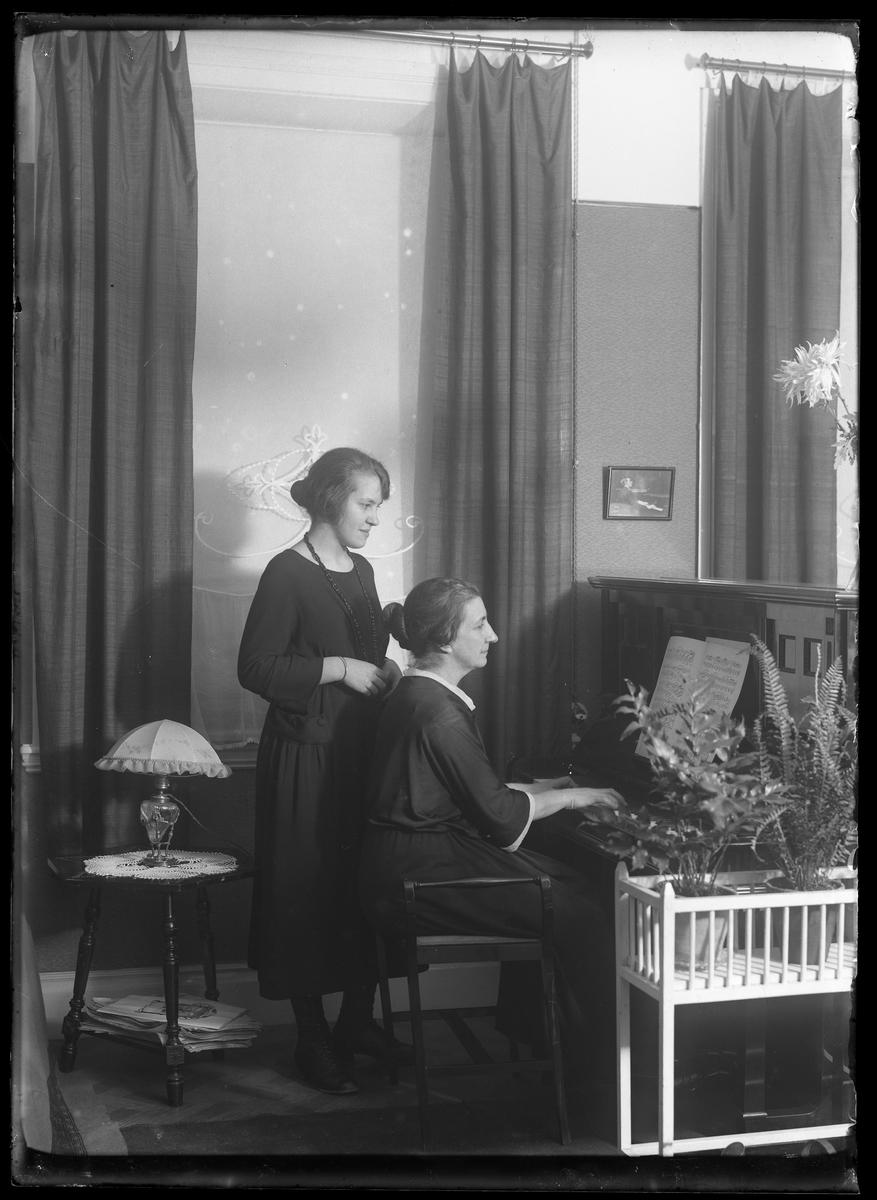 Fru Lenander sitter och spelar på ett piano medan hennes dotter står bredvid.