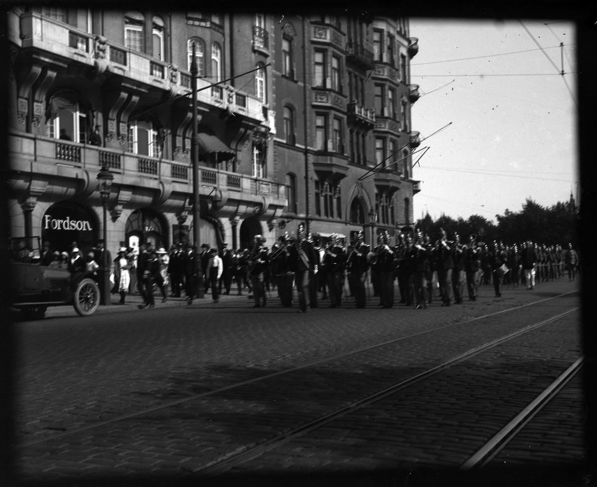 Gruppbild tagen under fotografen Harald Olssons excercistid. På en gata, troligen i Stockholm, marscherar militärer med musikkåren längst fram.