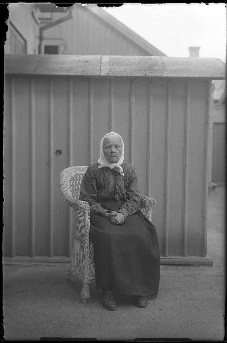 """En äldre kvinna sitter i en korgstol framför ett träplank eller en träbyggnad. I fotografens egna anteckningar står det """"[Beställning genom] Axel, Gumman 80år""""."""