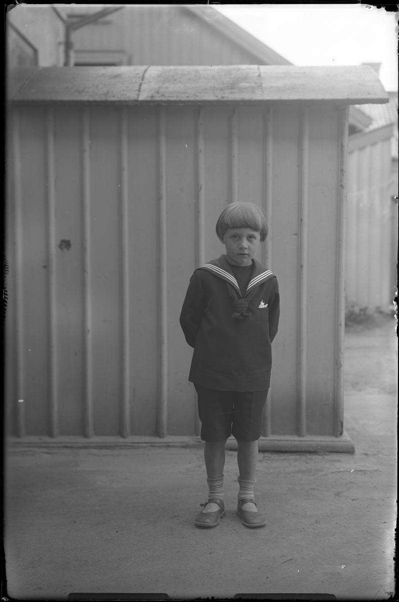 """En pojke i sjömansdräkt står framför ett träplank eller en träbyggnad. I fotografens egna anteckningar står det """"[Beställning genom] Axel, pojken""""."""