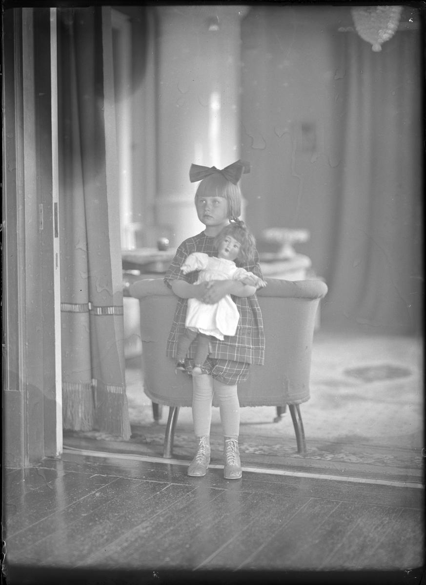 En flicka (Norinder i efternamn) klädd i rutig klänning och med rosett i håret står med en docka i famnen. I bakgrunden skymtar fåtöljer och en kakelugn.