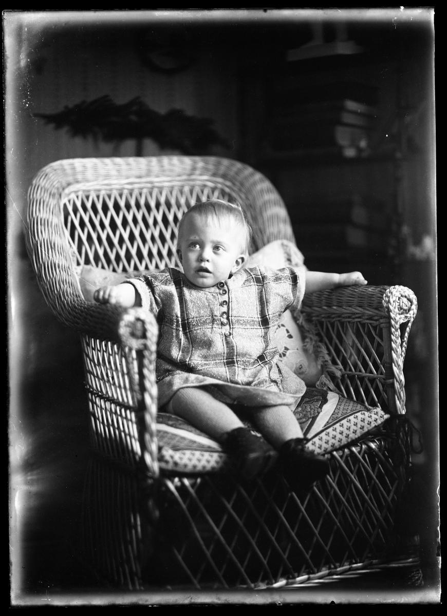 """En liten flicka i rutig klänning och svarta skor sitter i en korgstol. I fotografens egna anteckningar står det """"Richard Bergs flicka""""."""