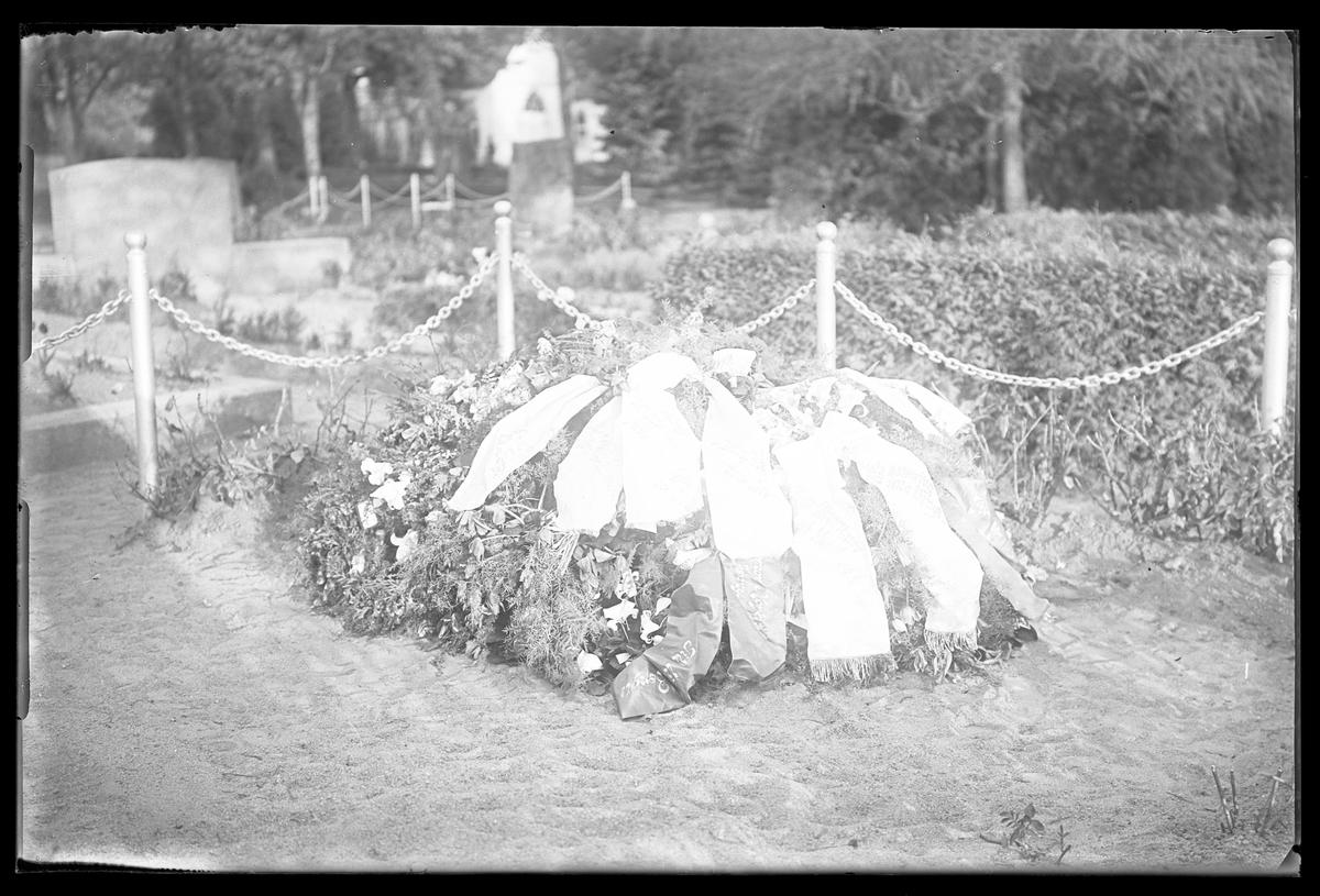 Bengt Nilssons grav täckt av blommor och band.