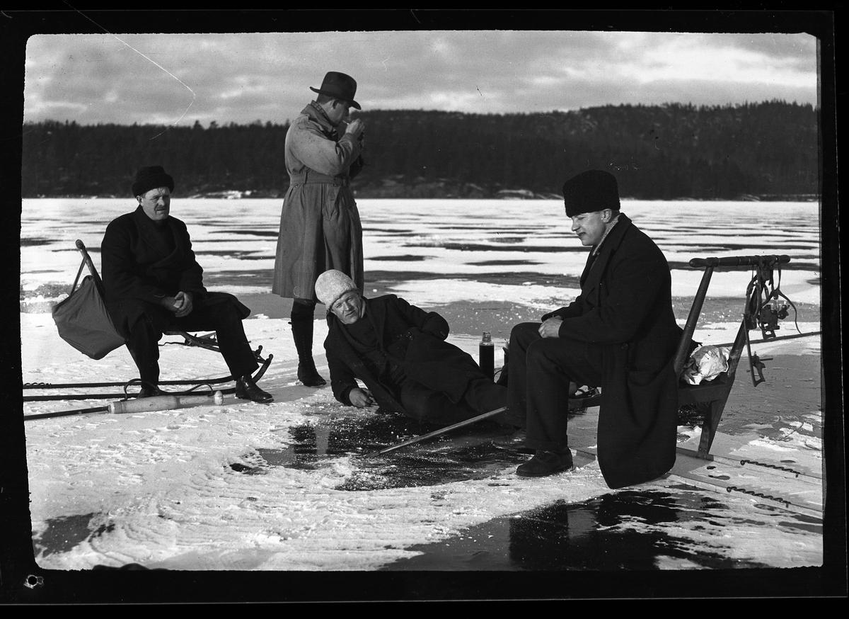 """Fyra män tar en fikapaus på isen vid vinterfiske. Två av dem sitter på varsin kälke, en ligger på isen och den står i bakgrunden och tänder en pipa. I fotografens egna anteckningar står det """"Fiske. Olle, Claesson, Bredborg & Sven""""."""