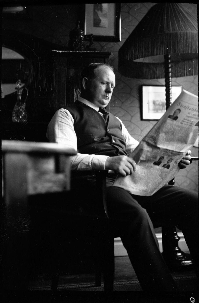 En man sitter i en länstol och läser en tidning.