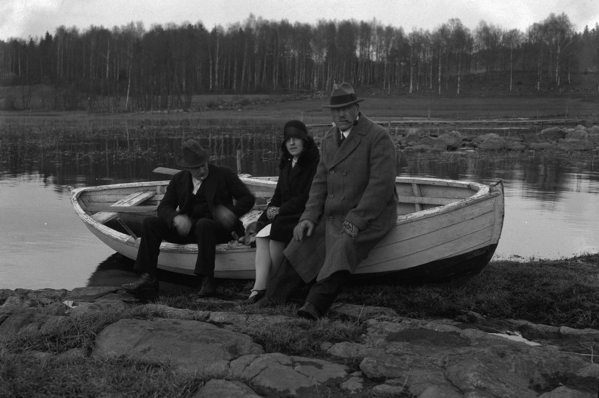 Tre personer sitter på kanten av en båt som halvt dragits upp på land. Kvinnan heter Lizzie Skoglund och mannen närmast henne är tolkad som Karl E Skoglund.