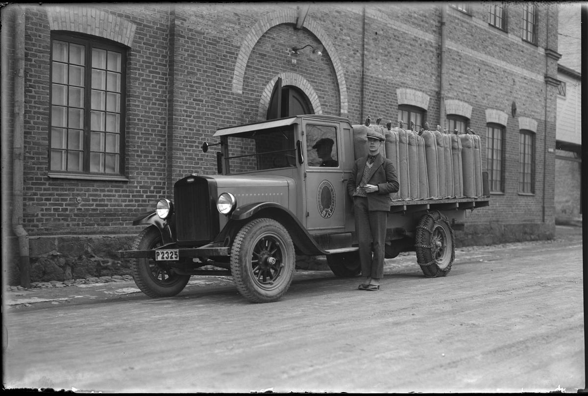 """En man med en pipa står lutad mot en lastbil. På bilens dörr syns loggan för Alingsås Bomullsväveri och på flaket är textilbalar lastade. I fotografens egna anteckningar står det """"Siöstedt med bilen"""". Eventuellt är det Stig Svante Siöstedt."""