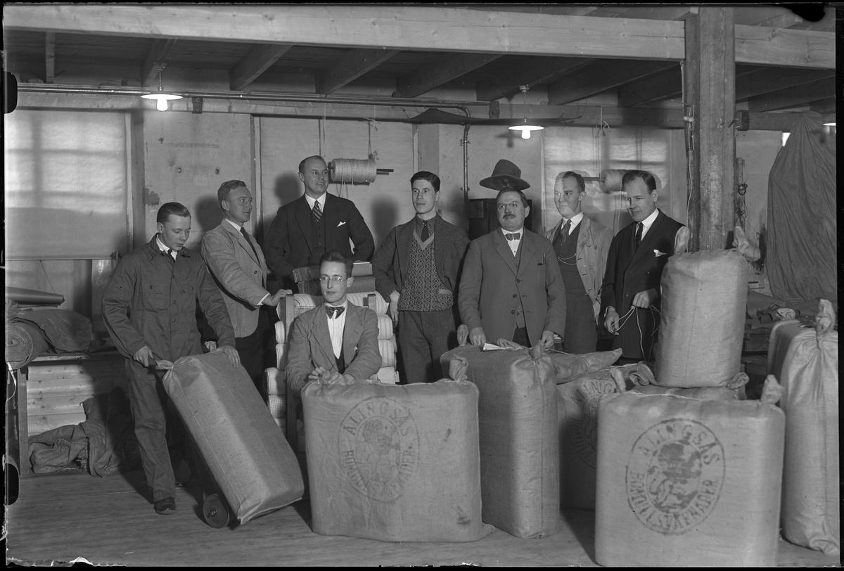 """Gruppbild på åtta män omgivna av textilbalar märkta """"Alingsås Bomullsväfnader"""". Mannen i mitten tolkad som Siöstedt (se bild AM HO 00848), troligen Stig Svante Siöstedt. I fotografens egna anteckningar står det """"Packargänget""""."""