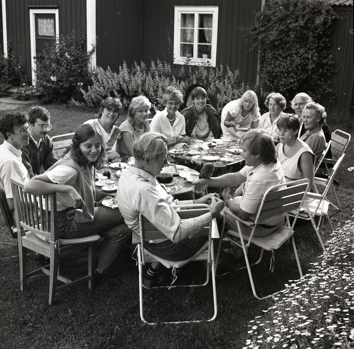 Kvinnor och män samlade runt ett kaffebord i en trädgård på Kristina-dagen 24 juli 1984.