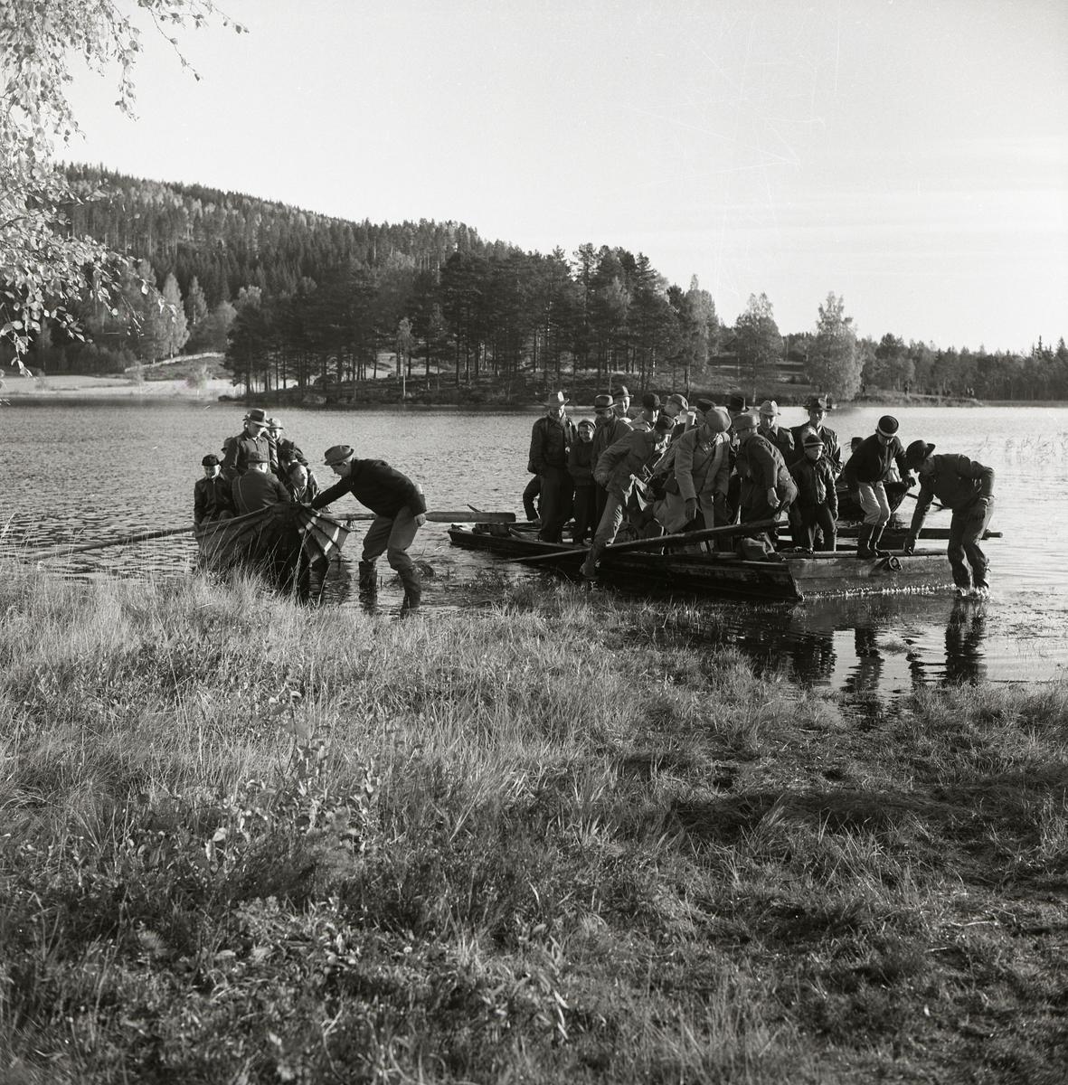 Några människor drar in en båt och en flotte till land vid sjön Stornien, 6 oktober 1957.
